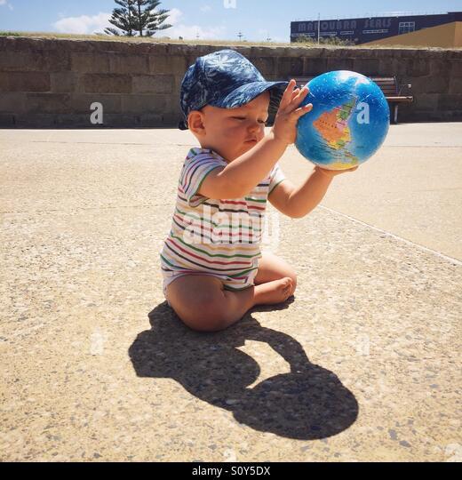 Kind spielt mit Globe Kugel Stockbild