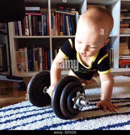 Kind spielt mit Fitnessgeräten Stockbild