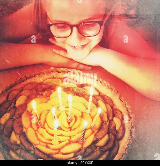 Kleines Mädchen mit Brille betrachten ihr Geburtstag Apfelkuchen mit 8 Kerzen Stockbild