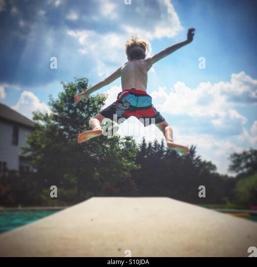 Ein kleiner Junge springt ein Sprungbrett und in einen Pool an einem heißen Sommertag Stockbild
