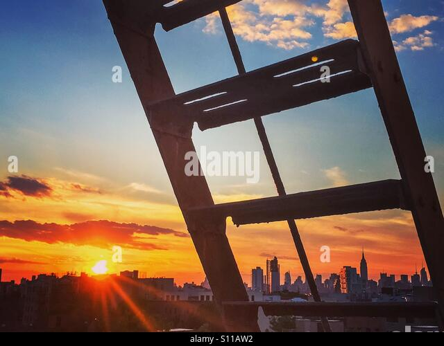 NYC Sonnenuntergang durch Fenster eines Mehrfamilienhauses in Williamsburg, Brooklyn. Stockbild