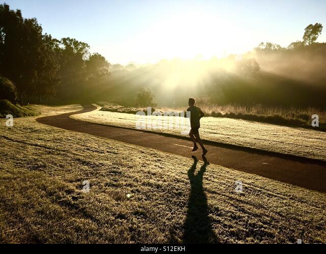 Ein Mann läuft durch das Licht des frühen Morgens in Clifton Hill, Melbourne, Victoria, Australien Stockbild