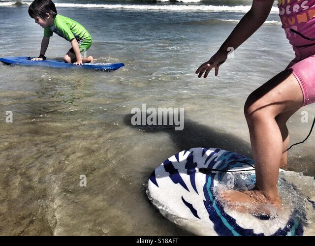Kleinkinder spielen mit Boogie Boards im Meer Stockbild