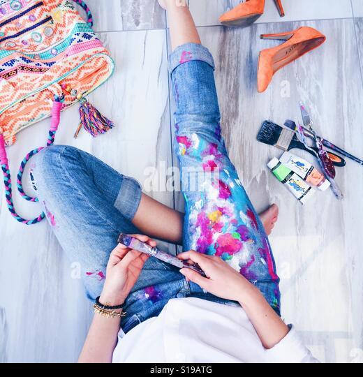 Künstler, entspannende tragen Farbe bedeckt Bluejeans mit Malzubehör und hell abgedeckt Tasche und Heels. - Stock-Bilder