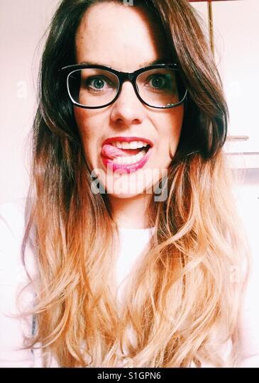 Verrücktes Mädchen mit Brille und rote Lippen Stockbild