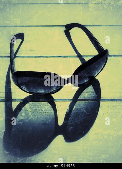 Retro-Sonnenbrille und lange Schatten, die den natürlichen Sonnenlicht auf blauem Hintergrund aus Holz. Schwere Stockbild