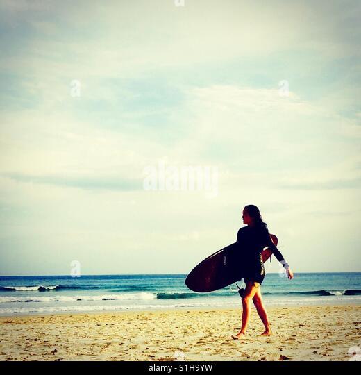 Australien, langen Surftag als Lebensstil, Mädchen zu Fuß mit dem Surfbrett auf den Sandstrand Stockbild