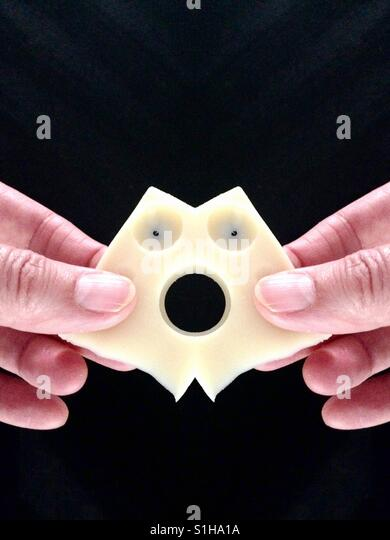 Sagen Sie 'Käse', Hände halten eine Scheibe Emmentaler Käse, das aussieht wie ein erschrockenen Stockbild