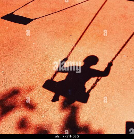 Schatten Sie-Spielplatz Stock von Kind auf Schaukel Stockbild
