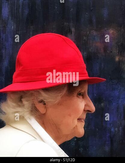 Dame im roten Hut, ein Besucher an der Royal Academy Sommerausstellung, London, UK Stockbild