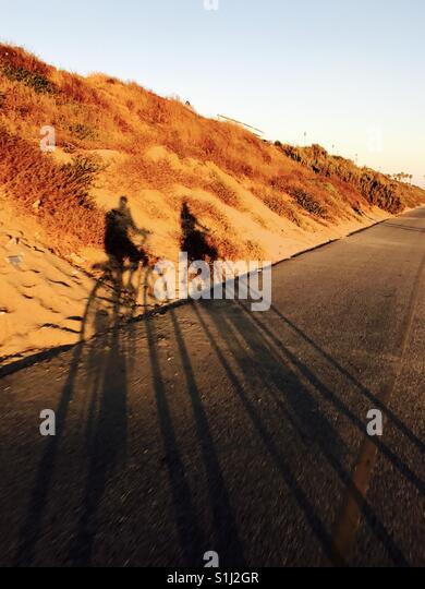 Schatten eines Mannes und einer Frau, Radfahren.  Strand El Segundo, Kalifornien USA Stockbild