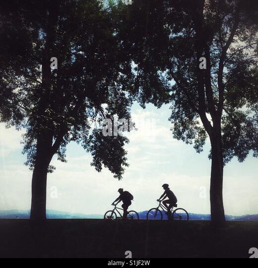 Silhouetten von zwei Radfahrer fahren hinter den Bäumen in der Nähe von Lake Coeur d'Allene in Idaho Stockbild