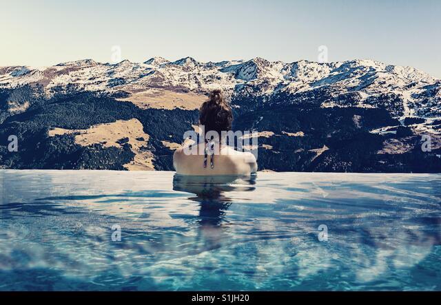 Frau Baden in einen Infinity-Pool mit Blick auf Schnee bedeckt Berge Stockbild