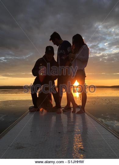 Freunde am Steg am See während des Sonnenuntergangs mit Hund Stockbild