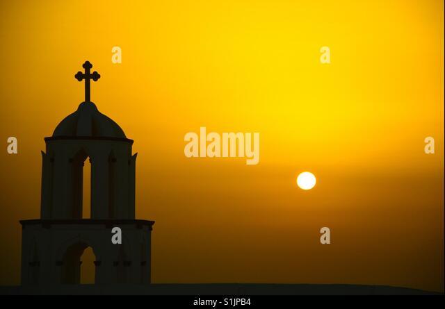 Silhouette einer orthodoxen Kirche bei Sonnenuntergang in Santorini Stockbild