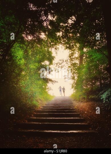 Zwei Kinder angerannt Steinstufen aus einem düsteren Wald ins freie Stockbild