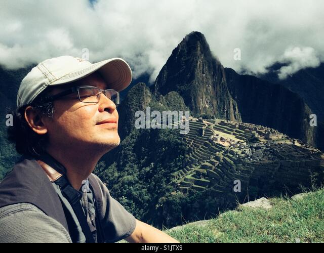 Applying Passform, die asiatischen Mann auf einer Terrasse mit Blick auf Machu Picchu in Peru meditiert Stockbild