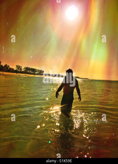 Mann zu Fuß an den Strand mit Sonnenlicht reflektieren das Wasser in Pemba, Mosambik, Afrika Stockbild