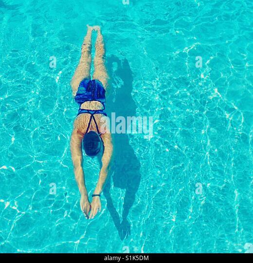 Frau an einem sonnigen Tag im Freibad schwimmen. Quadratische Ernte. Stockbild