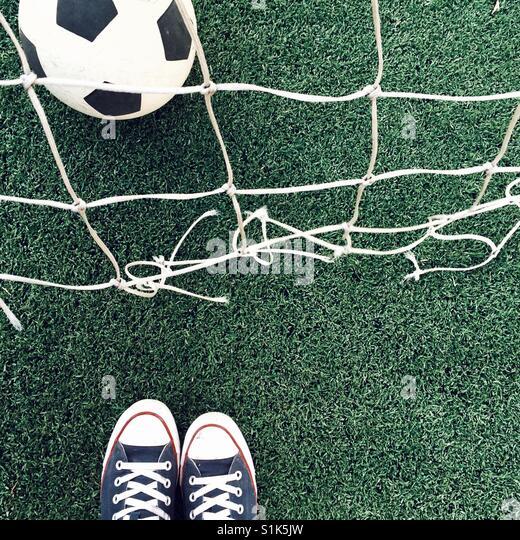 Fußball auf dem Feld und Füße Stockbild
