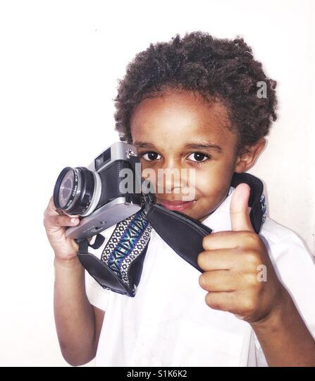 Junge mit einer Kamera macht ein Daumen hoch Zeichen Stockbild