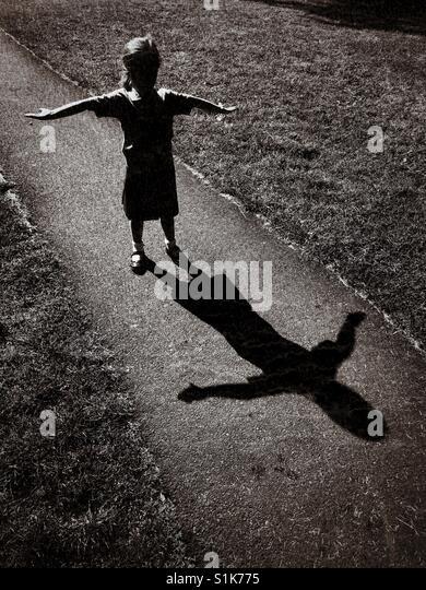 Schatten der ein 5 Jahre altes Kind als sie ihre Arme wirft und versucht, ein ' t ' Form. Ein Grunge-Effekt Stockbild