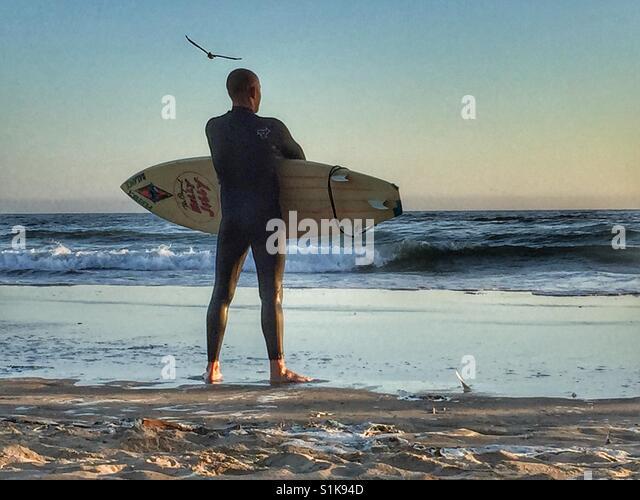 Rückansicht des erwachsenen männlichen Surfer mit Surfbrett unter dem Arm am Strand mit Blick auf das Stockbild