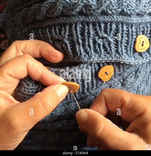 Persönliche Ansicht. Weibliche Hände Befestigung Herz geformt Holzknöpfe auf Strickpullover Stockbild