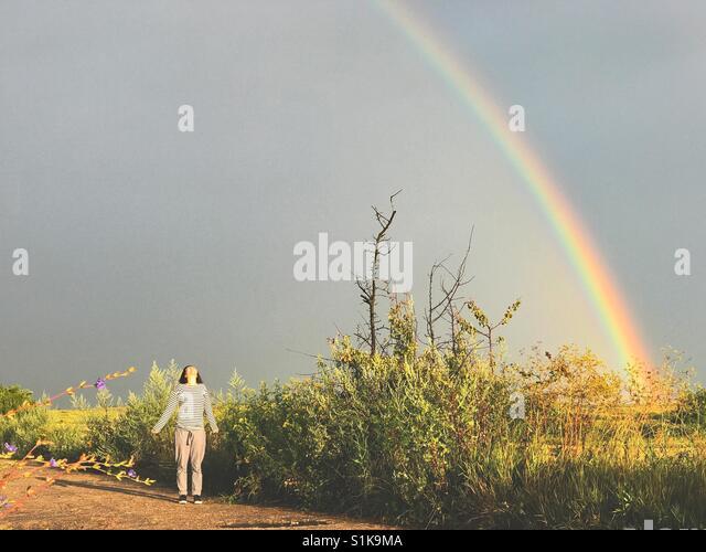 Frau stand unter einem Regenbogen Stockbild