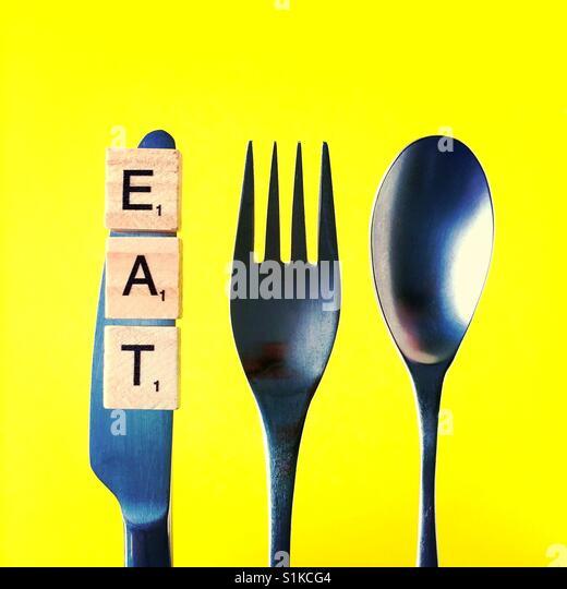 Eine obenliegende Nahaufnahme von einem Messer und einer Gabel und einem Löffel über einem gelben Hintergrund Stockbild
