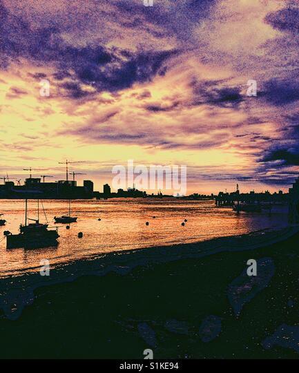 Fluss Themse romantischen Sonnenuntergang mit festgemachten Boote und dramatischer Himmel, Greenwich Peninsula, Stockbild