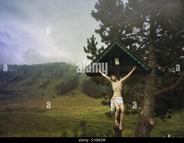 Eine Darstellung von Jesus Christus am Kreuz mit einem Berg und Wolken im Hintergrund Stockbild