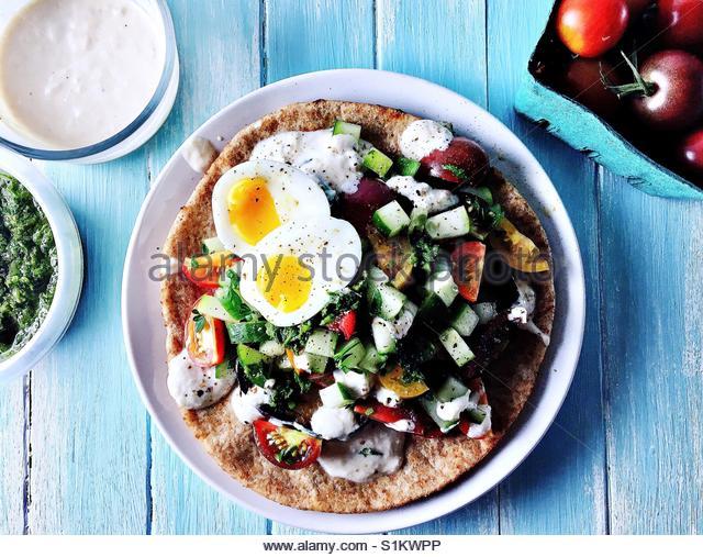 Sabih mit Sous vide weich gekochtes Ei auf weißen Teller auf blauen Holzplatte Hintergrund mit Korb mit Cherry Stockbild