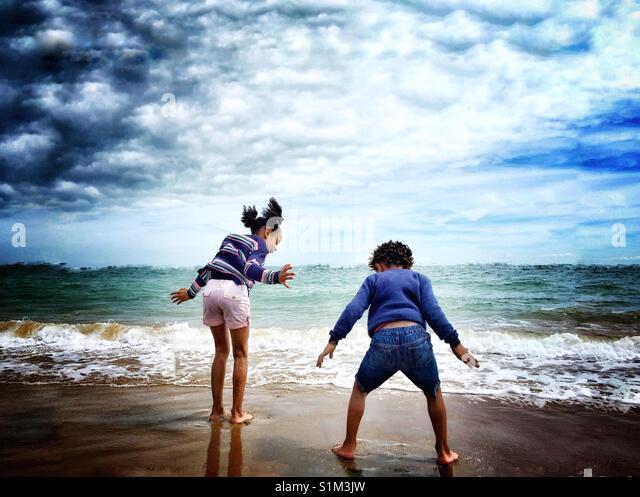 Zwei Kinder spielen am Strand. Stockbild