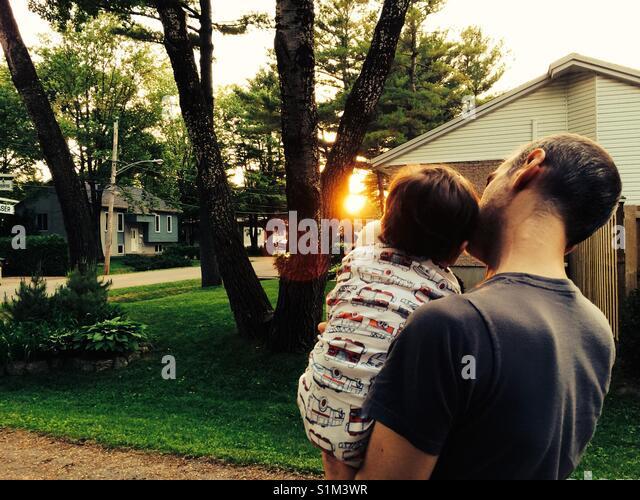Vater und Sohn den Sonnenuntergang in einer ruhigen Nachbarschaft Stockbild