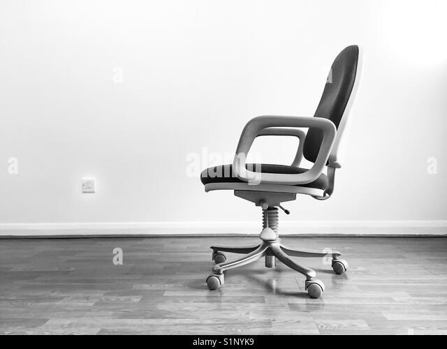 Ein drehstuhl in einem leeren Raum Stockbild