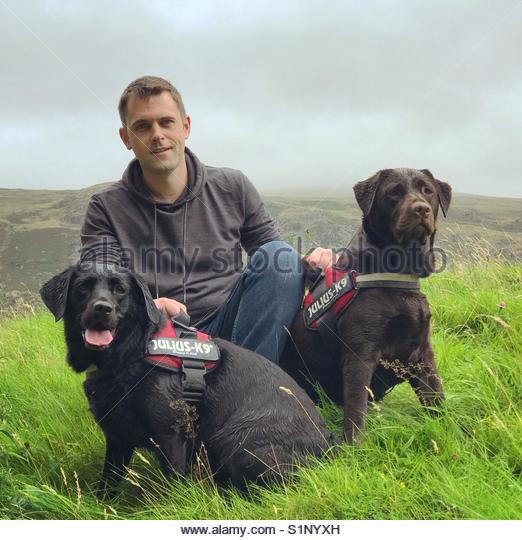 Mann sitzt mit Hunden in der Natur an einem regnerischen Tag Stockbild