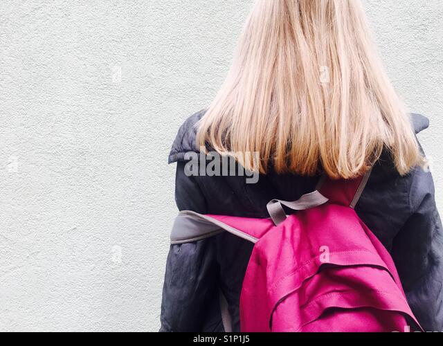 Eine Frau mit langen, blonden Haare mit Magenta pink Rucksack Stockbild