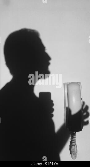 Schatten von einem Mann mit einem an der Wand befestigten Telefon Headset Stockbild