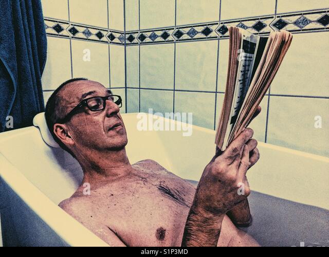 Im mittleren Alter Mann in Gläsern entspannt ein Buch lesen in der Badewanne Stockbild