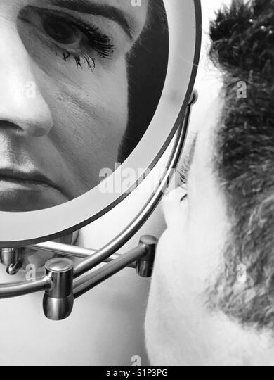 Eine schwarze und weiße Nahaufnahme einer Frau an ihr Spiegelbild in einem Make-up-Spiegel vergrößert Stockbild