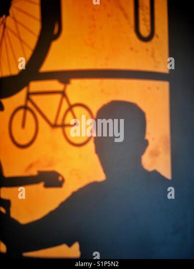 Schatten eines Mannes, der mit dem Zug reist mit dem Fahrrad Stockbild