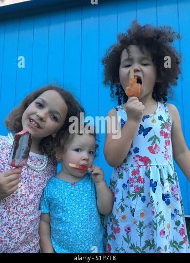 Mädchen essen Eis am Stiel Stockbild
