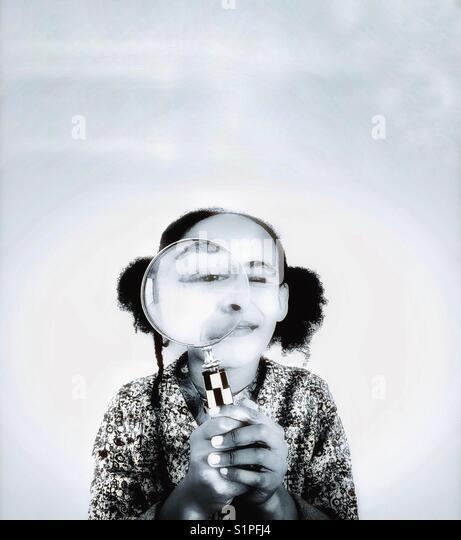 Ein junges Mädchen, das Spähen durch ein Vergrößerungsglas. Stockbild