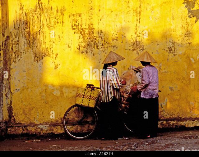 Dos mujeres con sombreros cónicos y bicicletas Hanoi, Vietnam. Imagen De Stock