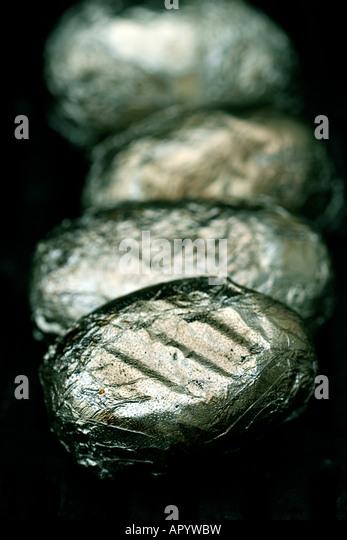 Las papas envueltas en aluminio sizzling en la Barbacoa Imagen De Stock