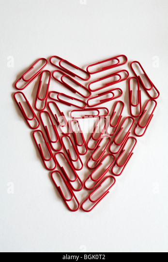 Concepto de romance de oficina - Corazón de papel rojo pinzas, clips, aislado sobre fondo blanco. Imagen De Stock