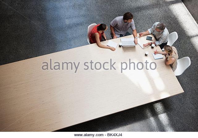 Los empresarios reunidos en mesa de conferencia Imagen De Stock