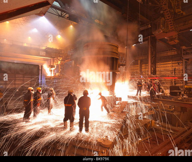 Los trabajadores con acero fundido en la planta Imagen De Stock