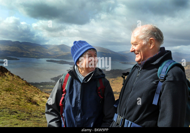 Personas mayores activas practicar el senderismo en el Parque Nacional de Trossachs, Escocia Imagen De Stock